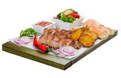 Varkensvleeskebab met plantaardige salade, aardappels en saus stock fotografie