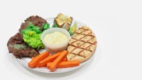Varkensvleeslapje vlees met een aardappel in de schil met boter en saladeroom vastgesteld h Royalty-vrije Stock Foto