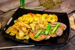 Varkensvleeslapje vlees met geroosterde aardappels en courgette Royalty-vrije Stock Afbeeldingen