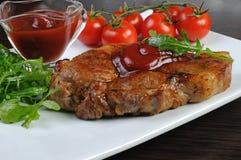 Varkensvleeslapje vlees met ketchup Stock Foto's