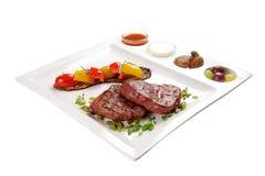 Varkensvleeslapje vlees met sausen en groenten Op een witte achtergrond stock afbeeldingen