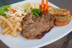 Varkensvleeslapje vlees op een lijst wordt geplaatst die stock afbeeldingen