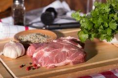 Varkensvleeslapje vlees op een scherpe houten raad stock afbeeldingen