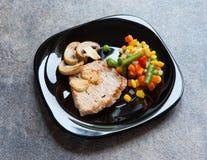 Varkensvleeslapje vlees op een zwarte plaat Stock Foto