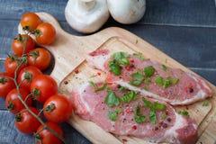 Varkensvleesplakken met kruiden en kruiden met een tak van kersentomaat Royalty-vrije Stock Afbeeldingen