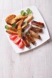 Varkensvleesribben, aardappels en tomaten op een verticaal van de plaat hoogste mening Stock Afbeelding