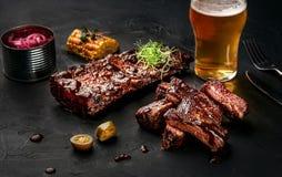 Varkensvleesribben in barbecuesaus en een glas bier op een zwarte leischotel Een grote snack aan bier op een donkere steenachterg stock afbeeldingen