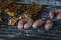 Varkensvleesribben en worst op een grill Stock Foto's