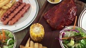 Varkensvleesribben met worsten en aardappels stock footage