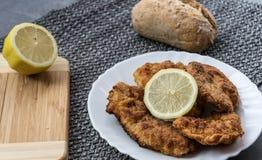 Varkensvleesschnitzel met citroen en gedobbelde aardappels Stock Afbeeldingen