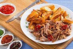 Varkensvleesschouder die in oven met gebraden aardappelwiggen wordt geroosterd royalty-vrije stock foto
