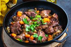 Varkensvleeswangen met groenten in een ijzer pan, gesneden brood worden gestoofd, olijfolie, met een donkere hierboven achtergron stock fotografie