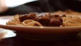 Varm ånga som kommer från ett italienskt klart mål Spagetti med kött i en platta på tabellen i ett kafé eller en restaurang tyck  lager videofilmer