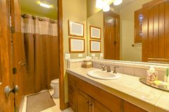 Varm badrumbelysning i det Kalifornien hemmet med sikt av en vask arkivbild