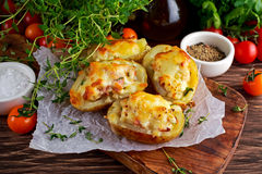 Varm bakad välfylld potatis med ost, bacon, persilja på trätabellen royaltyfri bild