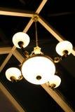 Varm belysning som är kommande ut från härliga lampor på tak Elektrisk lampa i mörker Tappninglampa i ett kafé Abstrakt lampa på  Royaltyfri Fotografi