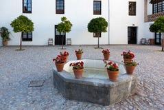 Varm borggård med brunnen eller springbrunnen i Spanien Arkivfoto