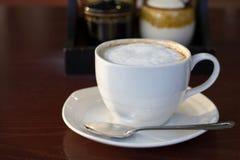 Varm cappuccino i den vita koppen royaltyfri foto