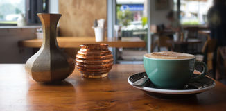 Varm cappuccino på en tabell inom en coffee shop Royaltyfri Foto