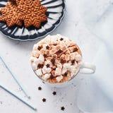 Varm choklad eller kakao med den piskade kräm- och marshmallowgodisen och julpepparkakakakor royaltyfria foton