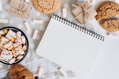 Varm choklad eller kakao med marshmallowen, kakor, anteckningsbok med på vit bakgrund royaltyfri foto