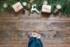 Varm choklad för jul i kvinnlig hand på träbakgrunden med den lantliga dekoren för jul Utrymme för bästa sikt och kopierings Royaltyfri Fotografi