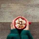 Varm choklad för jul med marshmallower i hand på träbakgrunden Bästa sikt med kopieringsutrymme Royaltyfria Foton
