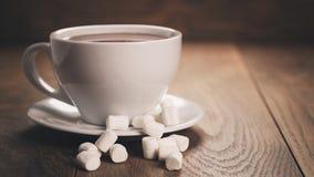 Varm choklad i cappuccinokopp med marshmallower på den wood tabellen Fotografering för Bildbyråer