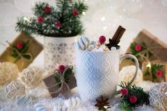 Varm choklad i en vit kopp med marshmallower och julgåvor på den ljusa ljusa bakgrunden Royaltyfri Foto