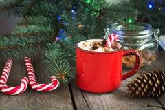 Varm choklad/kaffe med marshmallower och godisrottingen på träbakgrunden Juldekor för feriekort Royaltyfria Bilder