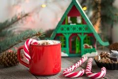 Varm choklad/kaffe med marshmallower och godisrottingen på träbakgrunden Juldekor för feriekort Royaltyfri Foto