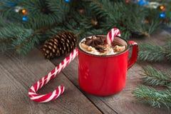 Varm choklad/kaffe med marshmallower och godisrottingen på träbakgrunden Juldekor för feriekort Arkivbild