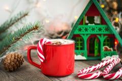 Varm choklad/kaffe med marshmallower och godisrottingen på träbakgrunden Juldekor för feriekort Arkivbilder