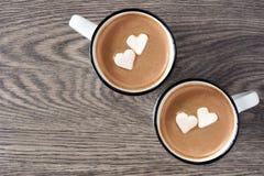 Varm choklad med hjärtamarshmallower över trä Arkivbild