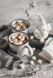 Varm choklad med marshmallower, keramiska Santa Claus, den gamla boken och handskar Fotografering för Bildbyråer