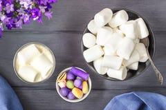 Varm choklad med marshmallower och godisrottingar på svart trä ta Royaltyfri Foto