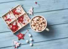 Varm choklad med marshmallower och kanel, julgarneringar på en blå träbakgrund vita röda stjärnor för abstrakt för bakgrundsjul m Arkivbilder