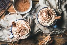 Varm choklad med piskat kräm, kanel, muttrar och kakaopulver Arkivfoto