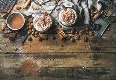 Varm choklad med piskat kräm, muttrar, kryddor och kakaopulver Arkivfoto