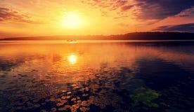 Varm dimmig morgon på floden majestätisk solnedgång Färgrika moln i himlen gloving i solljus Royaltyfri Bild