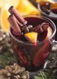 Varm drink för hemlagad jul i exponeringsglaskopp med art, kanelbruna pinnar och orange skivor på en träbakgrund överkant royaltyfri bild