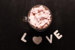 varm drink i en exponeringsglaskopp med rosa marshmallower arkivbilder
