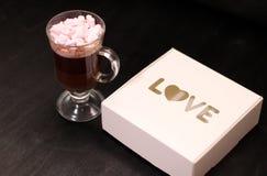 varm drink i en exponeringsglaskopp med rosa marshmallower royaltyfri fotografi