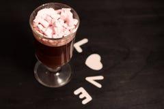 varm drink i en exponeringsglaskopp med rosa marshmallower royaltyfria foton