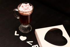 varm drink i en exponeringsglaskopp med rosa marshmallower royaltyfria bilder