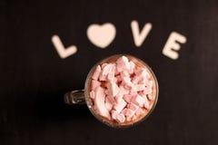 varm drink i en exponeringsglaskopp med rosa marshmallower arkivfoton