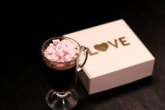 varm drink i en exponeringsglaskopp med rosa marshmallower fotografering för bildbyråer