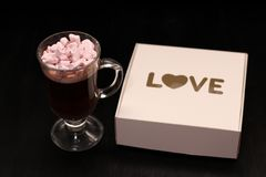 varm drink i en exponeringsglaskopp med rosa marshmallower arkivbild