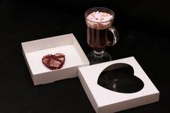 varm drink i en exponeringsglaskopp med rosa marshmallower och den vita asken med en genomskinlig räkning i form av hjärta med ka royaltyfri bild