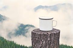 Varm drink utomhus på bakgrunden av de dimmiga bergen Royaltyfri Fotografi